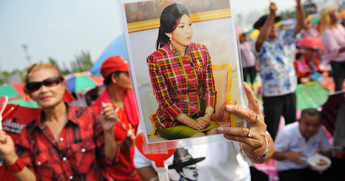 A pro-government red shirt supporter holds up a portrait of caretaker Prime Minister Yingluck Shinawatra at a large rally on March 15, 2014 in Ayutthaya, Thailand.</p>