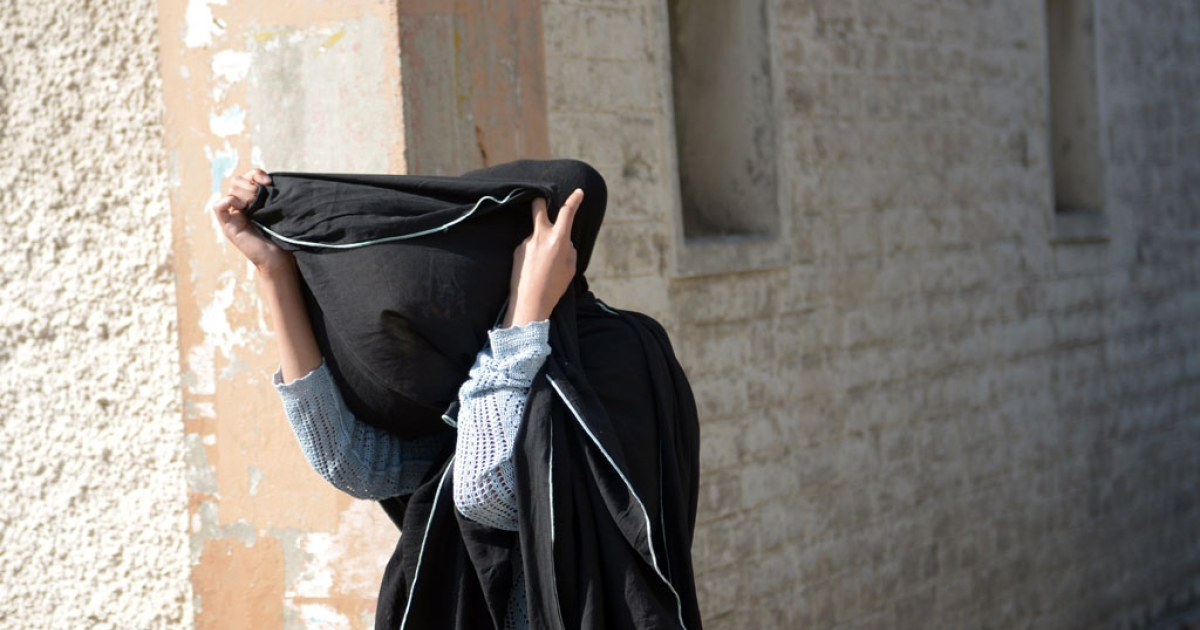 British prisoner Khadija Shah, who was convicted of attempting to smuggle narcotics, covers her face as she walks past photographers in Rawalpindi, Pakistan, on March 18, 2014.</p>