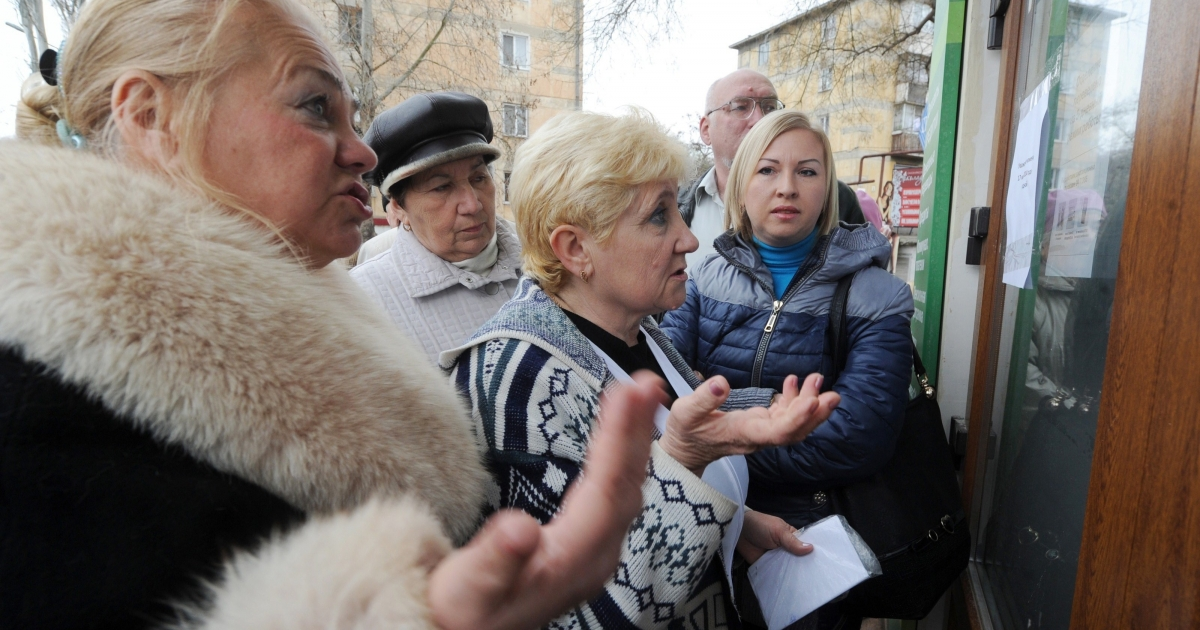 Smooth sailing? People react to closed doors at a bank in the Crimean city of Sevastopol.</p>