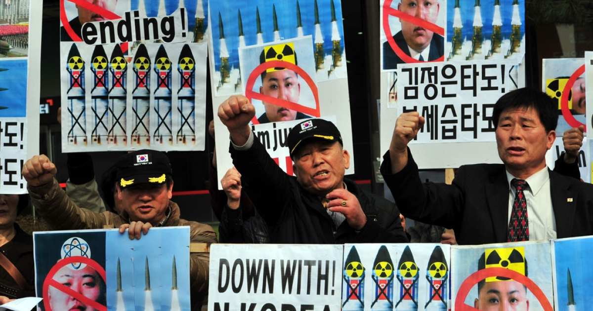 South Korean conservative activists chant slogans with placards showing portrait of North Korean leader Kim Jong-Un during a rally denouncing North Korea's missile test-launch in Seoul on March 26, 2014.</p>