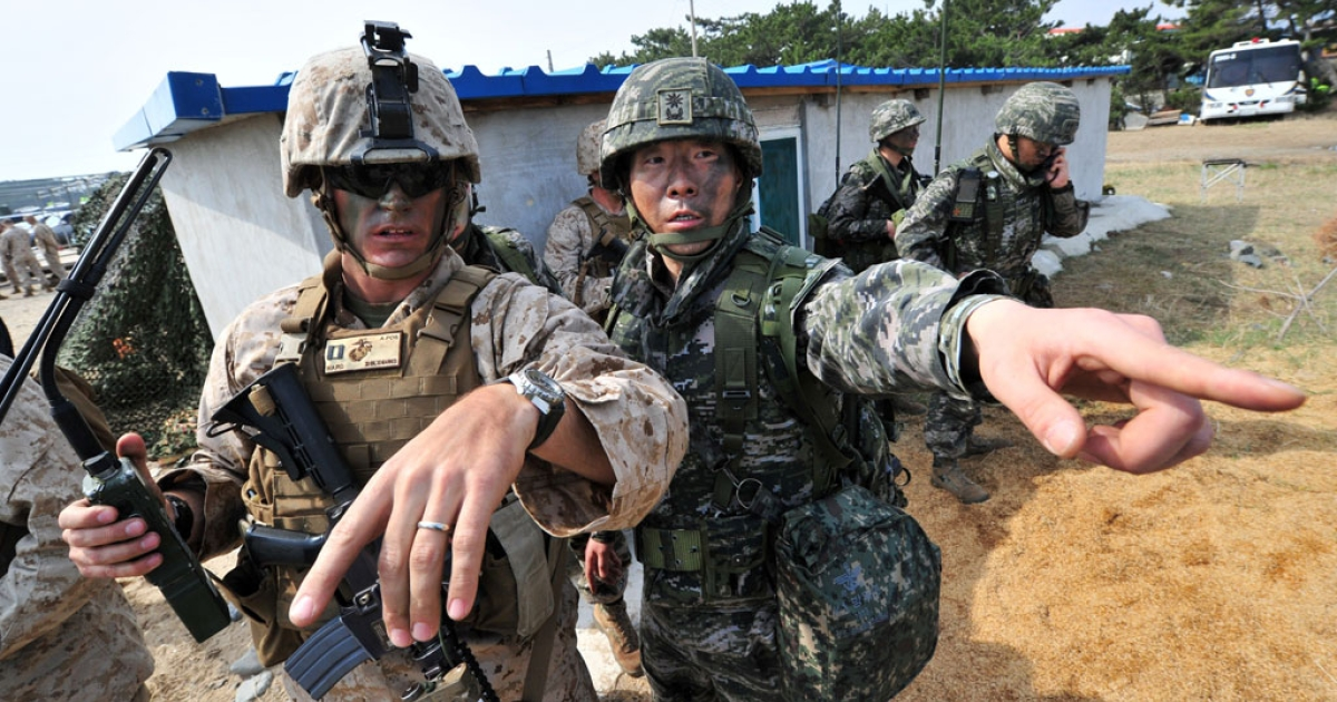 South Korean (R) and US (L) Marines gesture to a point during a joint landing operation by US and South Korean Marines in Pohang, southeast of Seoul, on March 31, 2014.</p>