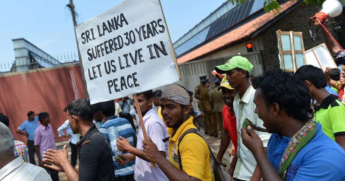 Sri Lankan Tamil pro-government activists take part in a demonstration outside the British High Commission in Colombo on March 20, 2014.</p>