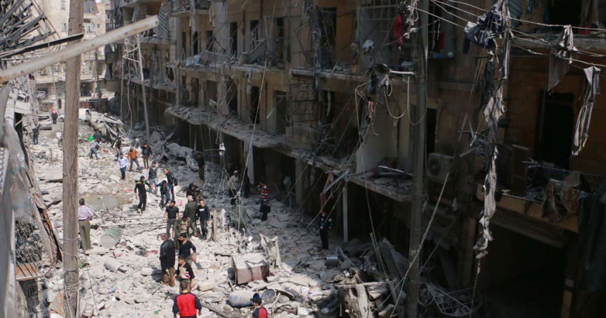 Syrians walk amid debris in a residential block reportedly hit by an explosives-filled barrel dropped by a government forces helicopter on March 18, 2014 in the northern city of Aleppo.</p>