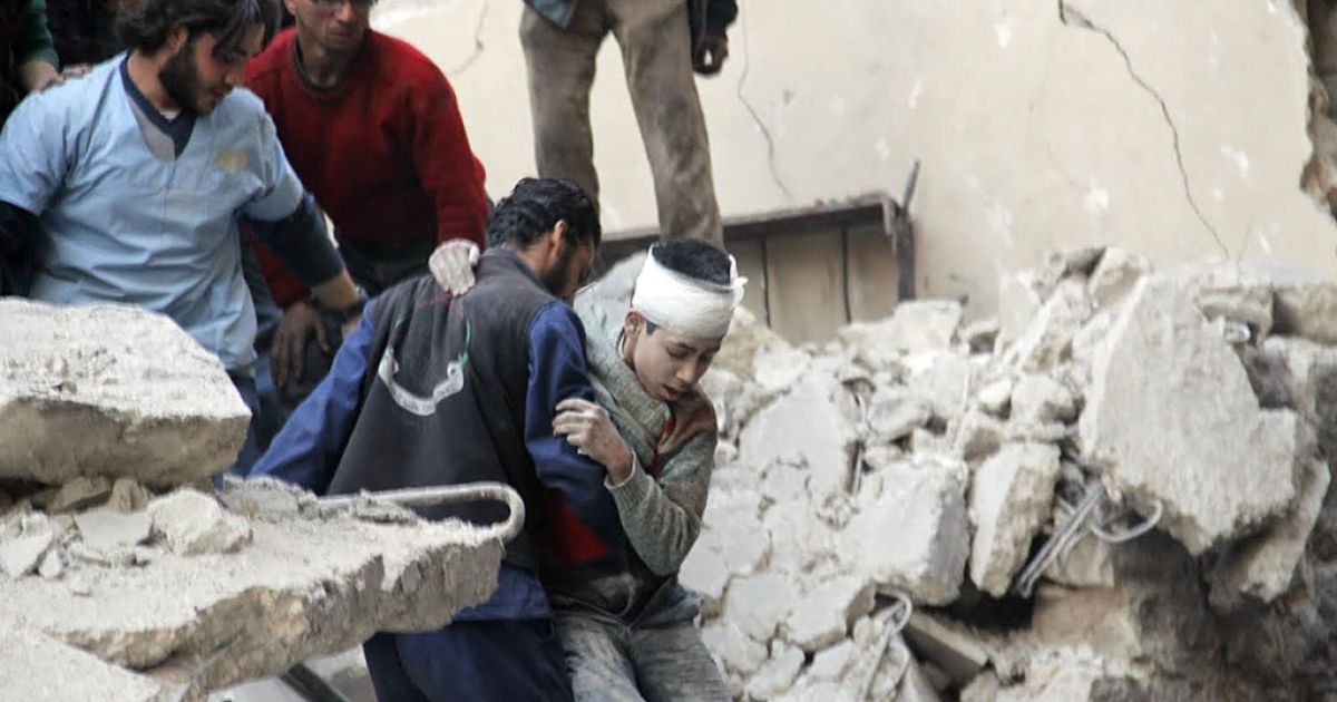 Syrian men rescue a wounded boy from the rubble of a destroyed building following a reported air strike by Syrian government forces on the Kallassa neighborhood in the northern city of Aleppo on Feb. 26, 2014.</p>
