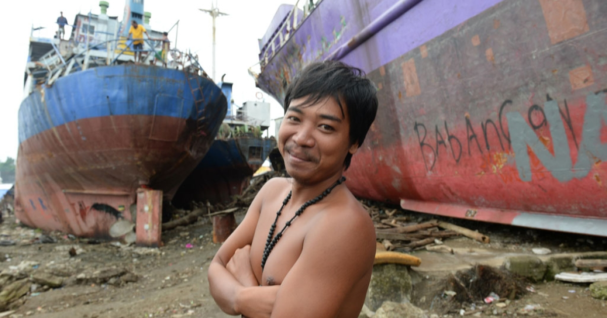 A resident stands next to cargo ships washed ashore during Typhoon Haiyan along the coastal area of Tacloban City in the Philippines on February 14, 2014. The devastating typhoon hit the city on Nov. 8, 2013.</p>