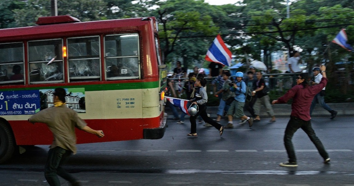 Thai opposition protesters throw rocks at a bus carrying pro-government Red Shirt supporters on their way to a rally at a stadium in Bangkok on November 30, 2013. The Red Shirts are preparing for armed resistance in the event that their government is overthrown by yet another coup.</p>