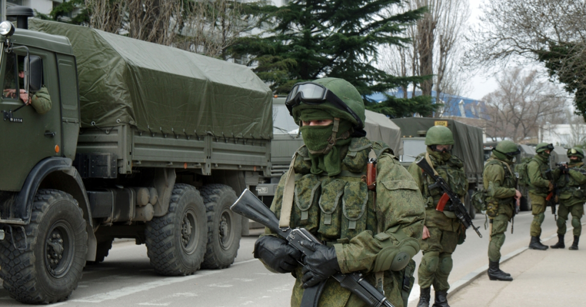 Unidentified soldiers with armored vehicles block the base of the Ukrainian border guard service in Sevastopol, on March 1, 2014.</p>