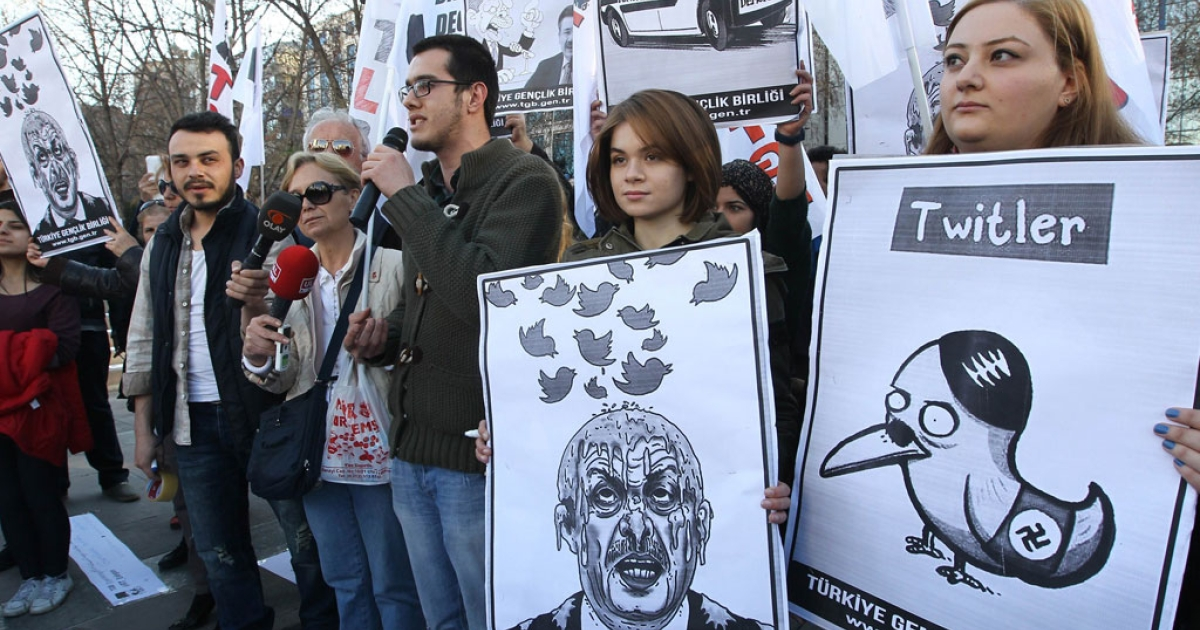 People hold placards as they protest against Turkey's Prime Minister Tayyip Erdogan after the government blocked access to Twitter in Ankara, on March 21, 2014.</p>