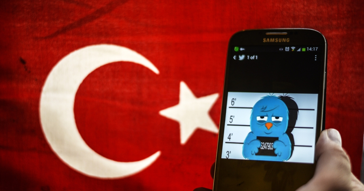 A picture representing a mugshot of the Twitter bird is seen on a smartphone with a Turkish flag in the background in Istanbul on March 26, 2014.</p>