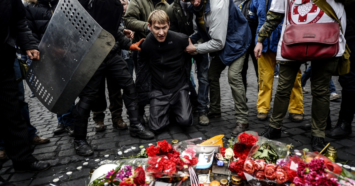 A man suspected of being a sniper and member of the pro-government forces is forced to pay his respects on February 22, 2014 to the mourning place of a victim killed in the clashes in Kyiv.</p>