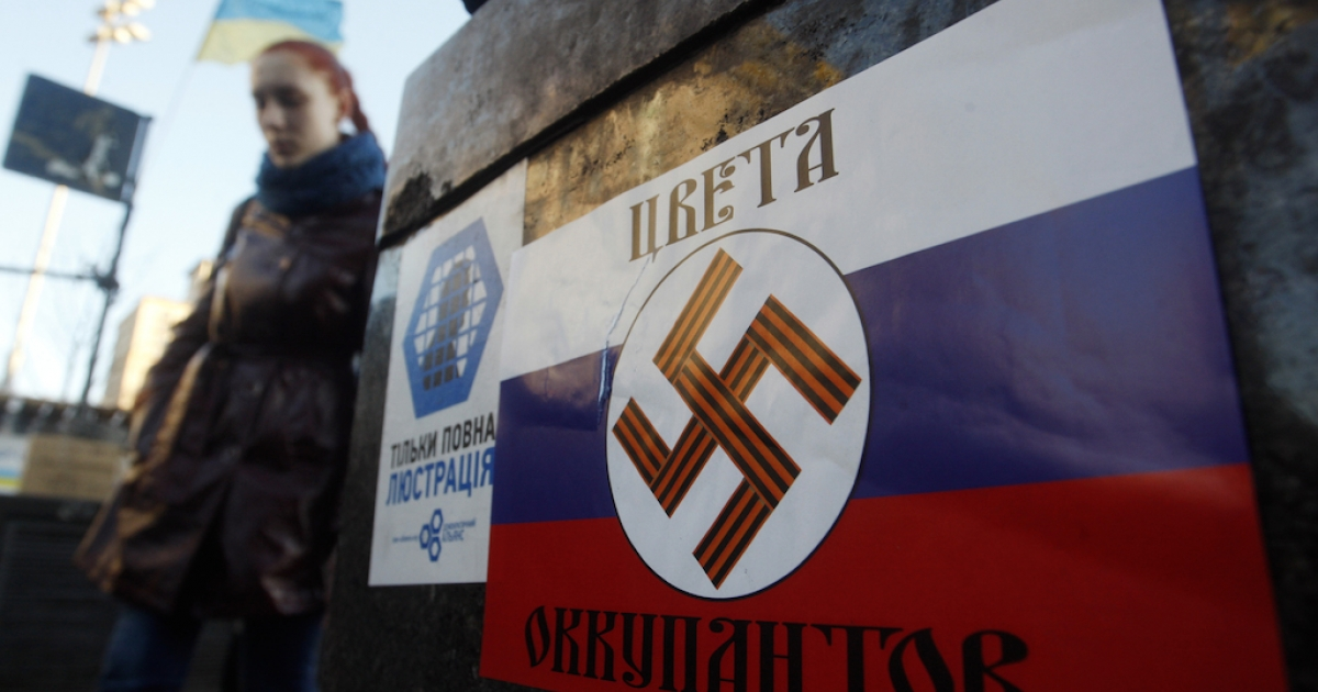 Both sides are guilty of spin. This photo taken in Independence Square in the Ukraine capital of Kyiv on March 12, 2014, shows a poster with a Nazi swastika overlaid on a Russian flag that says