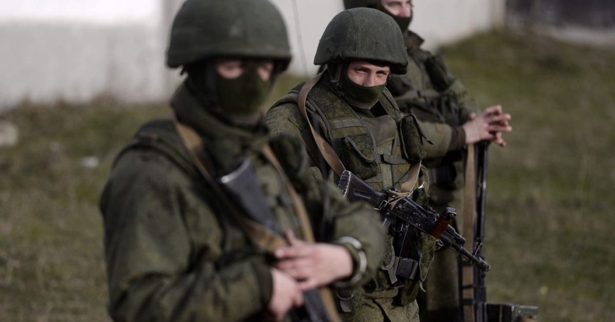 Armed men, believed to be Russian servicemen, stand guard outside a Ukrainian military base in Crimea on March 16, 2014.</p>