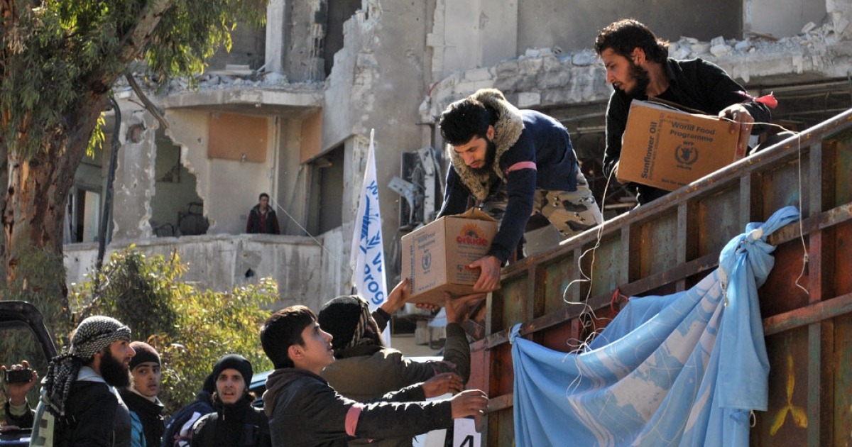 Rebel fighters help unload aid food during a UN-led humanitarian operation in the besieged Syrian city of Homs on Feb. 12, 2014.</p>