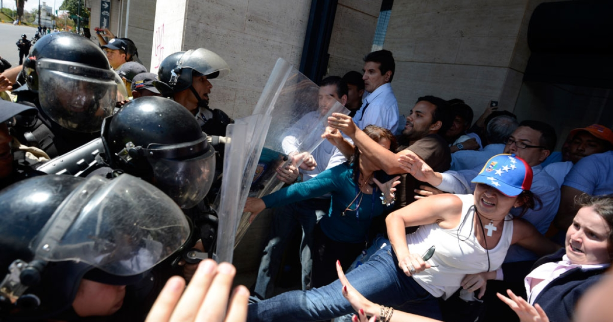 Venezuelan public health personnel scuffle with riot police during a protest in Caracas on March 10, 2014.</p>