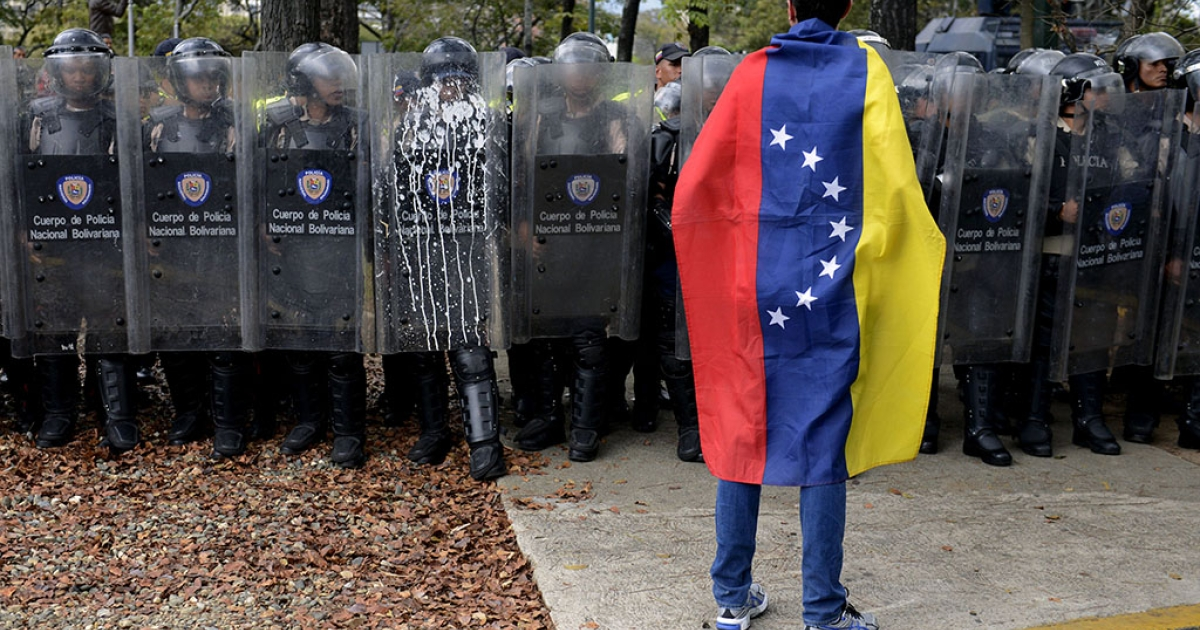 A Venezuelan student stands in front of riot police during a protest against the government of President Nicolas Maduro, in Caracas on March 12, 2014.</p>