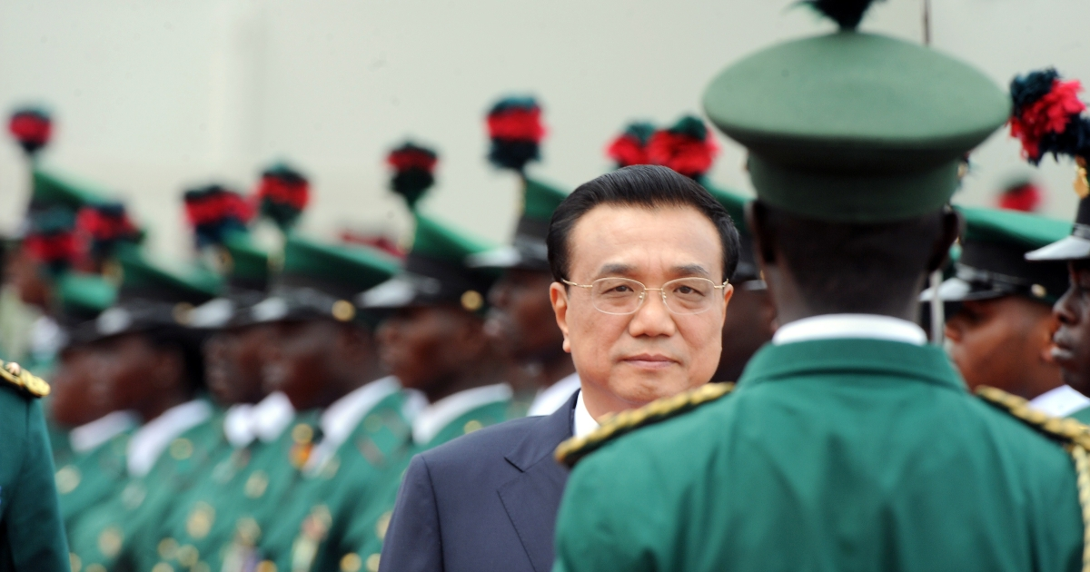 Chinese Prime Minister Li Keqiang reviews an honour guard at the presidential villa in Abuja, Nigeria.</p>
