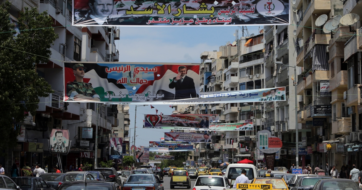 Election campaign posters bearing portraits of President Bashar al-Assad hang over a street in Syria's Mediterranean port city of Latakia.</p>