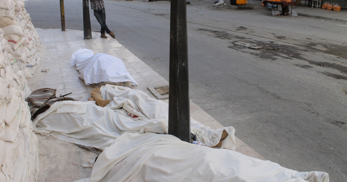 A man stands looking at bodies wrapped in shrouds lying on the ground following a reported air strike by government forces on May 30, 2014 in Aleppo.</p>