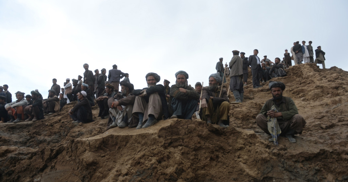 Afghan villagers gather at the site of a landslide in the Argo district of Badakhshan province on May 3, 2014.</p>