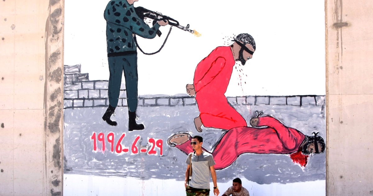 Libyan security guards are pictured in front of a mural painting depicting a torture scene outside Tripoli's Abu Slim jail, where a masscare of  1,200 prisoners took place in 1996.</p>