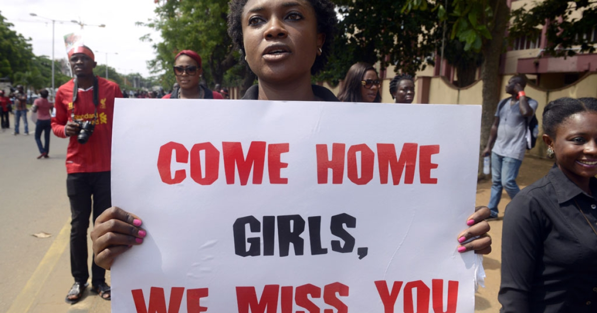 A woman carries a placard to press for the release of missing Chibok schoolgirls during a rally by civil society in Lagos on May 5, 2014.</p>