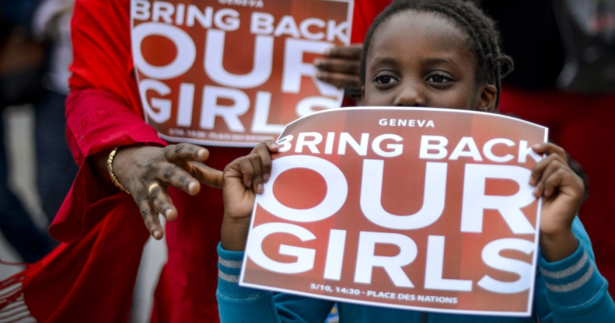 A young participant shows a placard during a demonstration in Geneva for the release of the abducted Nigerian schoolgirls on May 10, 2014.</p>