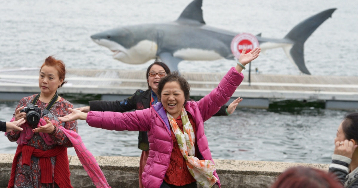 Chinese tourists pose for a photo in front of 24-foot great white shark replica in Sydney on Nov. 26, 2013.</p>