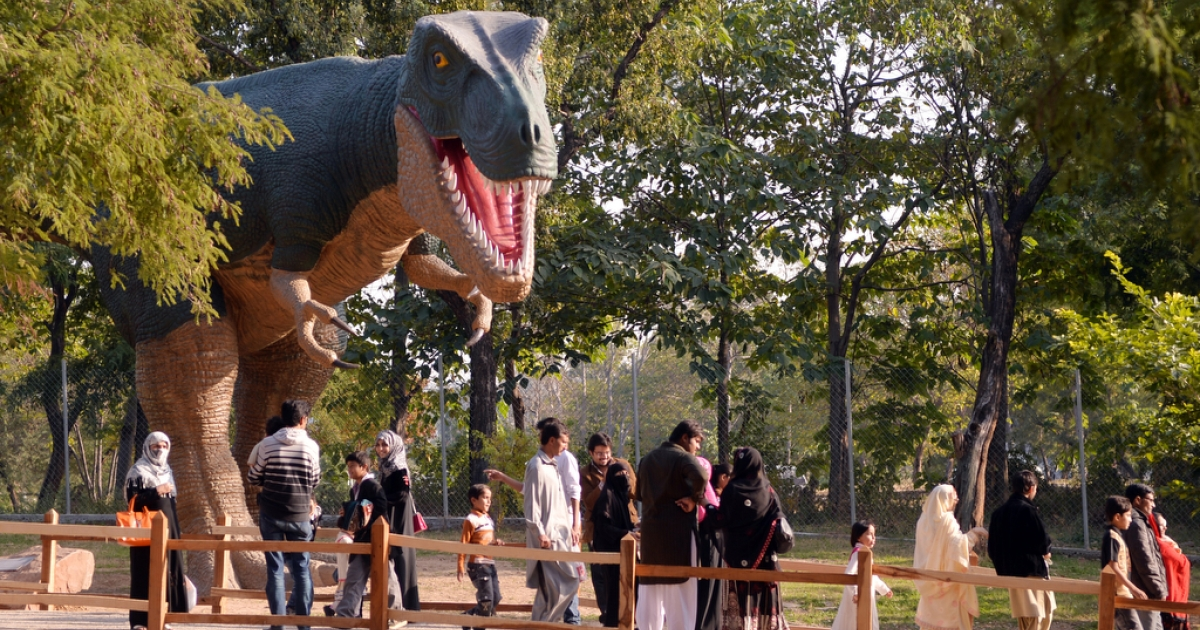 Visitors walks past a model of a dinosaur at the Marghzar Zoo in Islamabad on Nov. 24, 2013.</p>