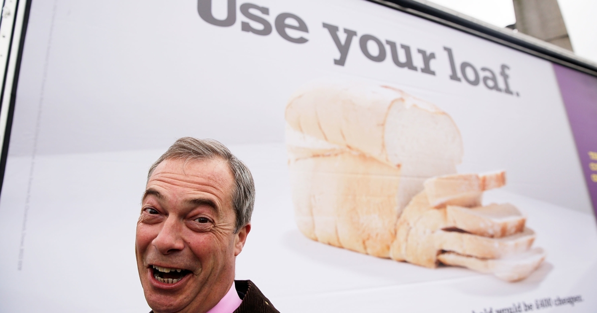 Farage under a UKIP campaign poster for the European elections.</p>