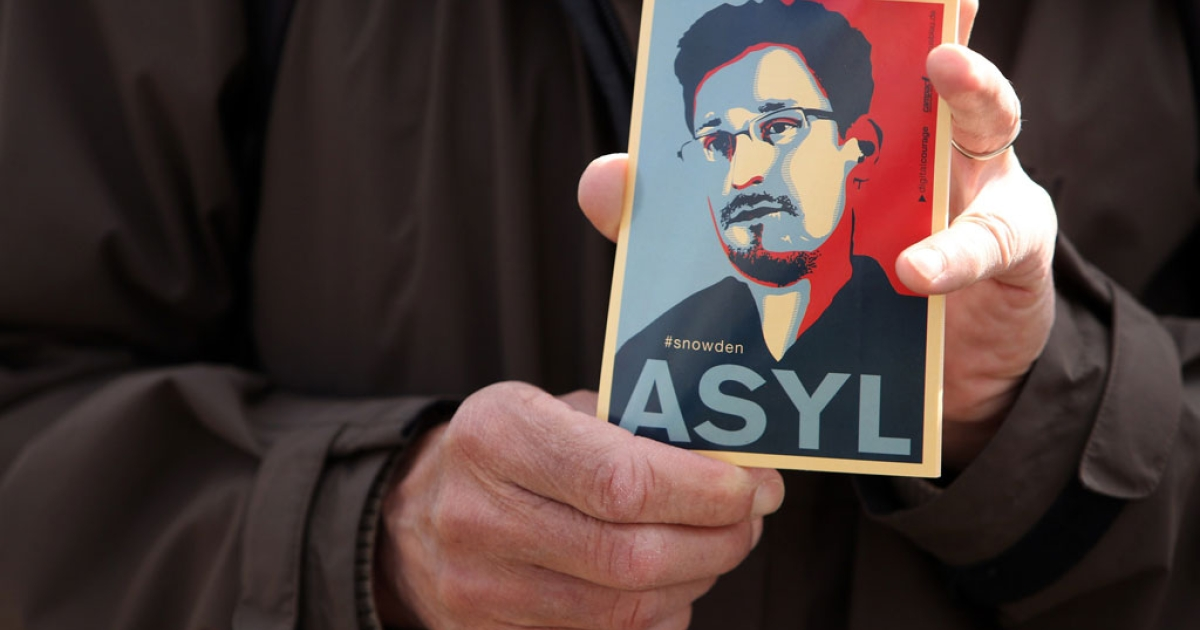 A demonstrator holds a card depicting fugitive US intelligence leaker Edward Snowden during a demonstration in Berlin in favor of an appearance by Snowden as a witness in German NSA hearings on May 8, 2014.</p>