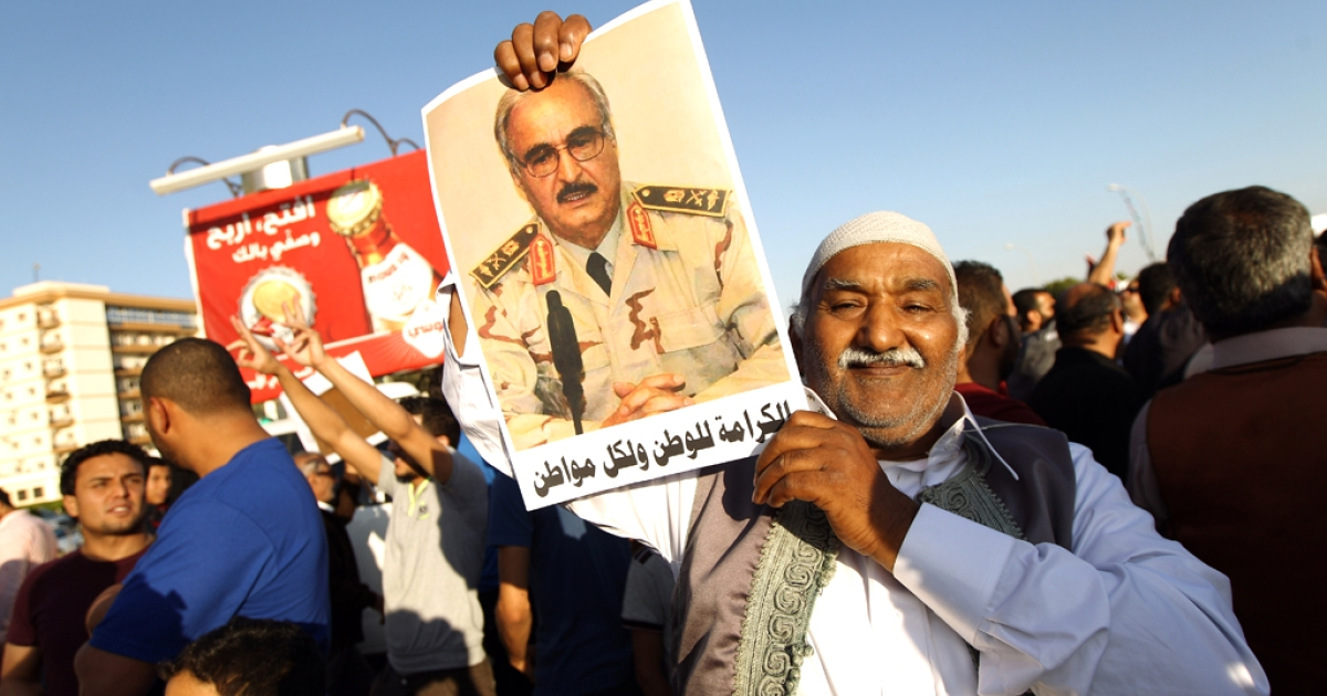 A Libyan carries a portrait of retired Gen. Khalifa Haftar during a rally in support of the rogue former general whose forces have launched a