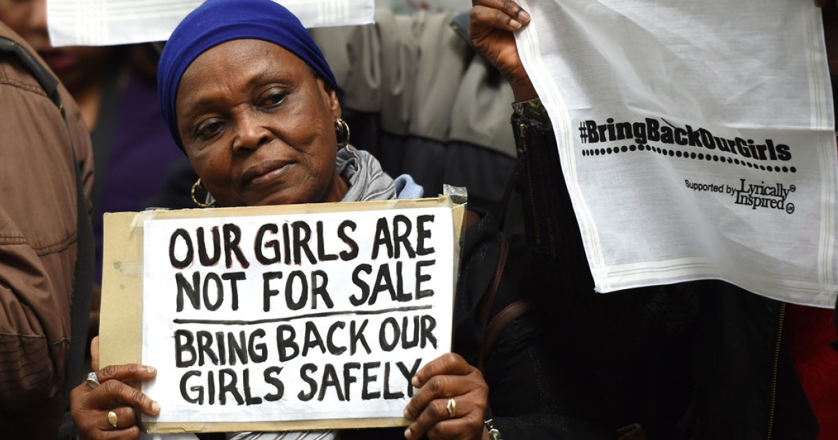 Protestors hold placards as they demonstrate outside Nigeria House in central London on May 9, 2014, to demand the return of more than 200 Nigerian schoolgirls abducted by the Boko Haram Islamist group.</p>