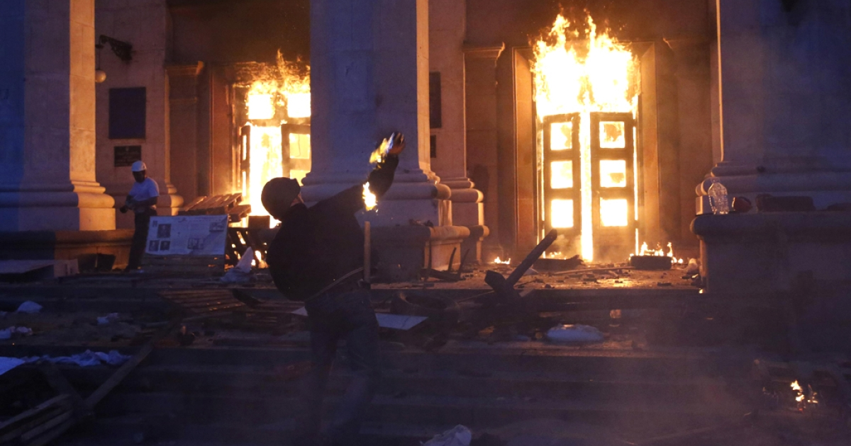 A protester throws a petrol bomb at the trade union building in Odessa May 2, 2014. At least 30 people were killed in a fire on Friday in the trade union building in the center of Ukraine's southern port city of Odessa, regional police said.</p>