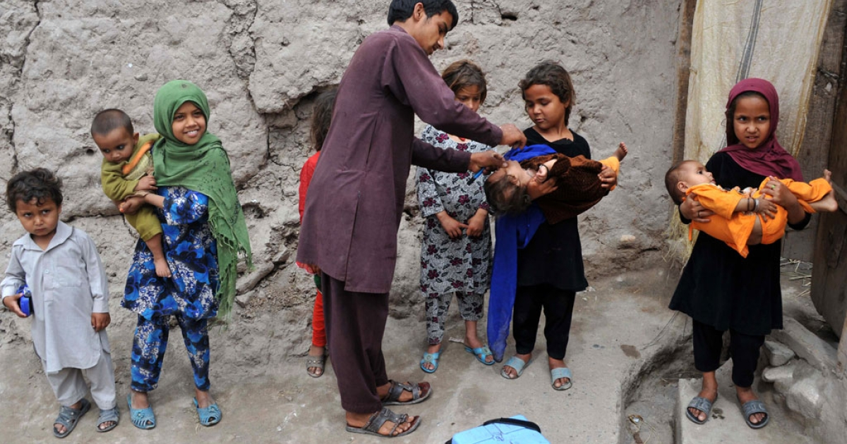 An Afghan health worker administers a polio vaccination to a child during a vaccination campaign on the outskirts of Jalalabad in Nangarhar province on May 4, 2014.</p>