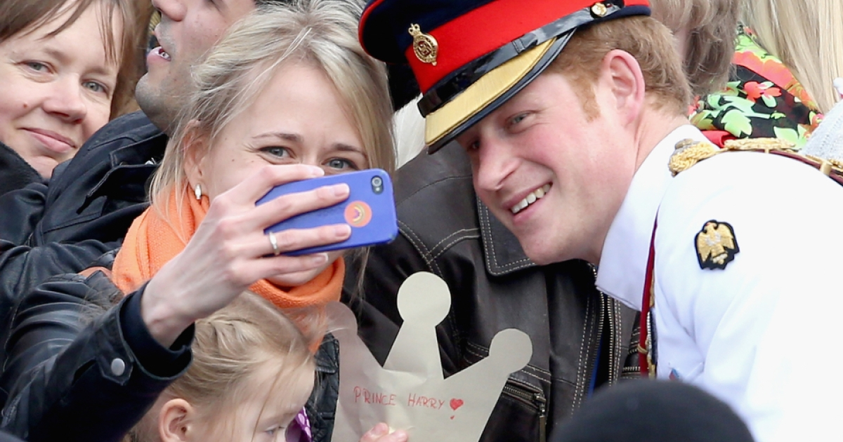 A woman takes a selfie with Prince Harry as he meets locals in the Estonian capital of Tallinn on May 16, 2014.</p>