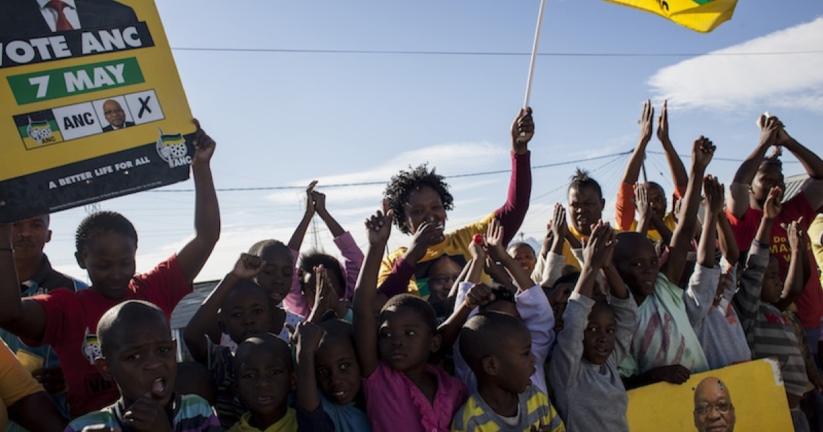 ANC supporters cheer on voters along the streets of Khayelitsha Township on May 7, 2014 in Cape Town, South Africa.</p>