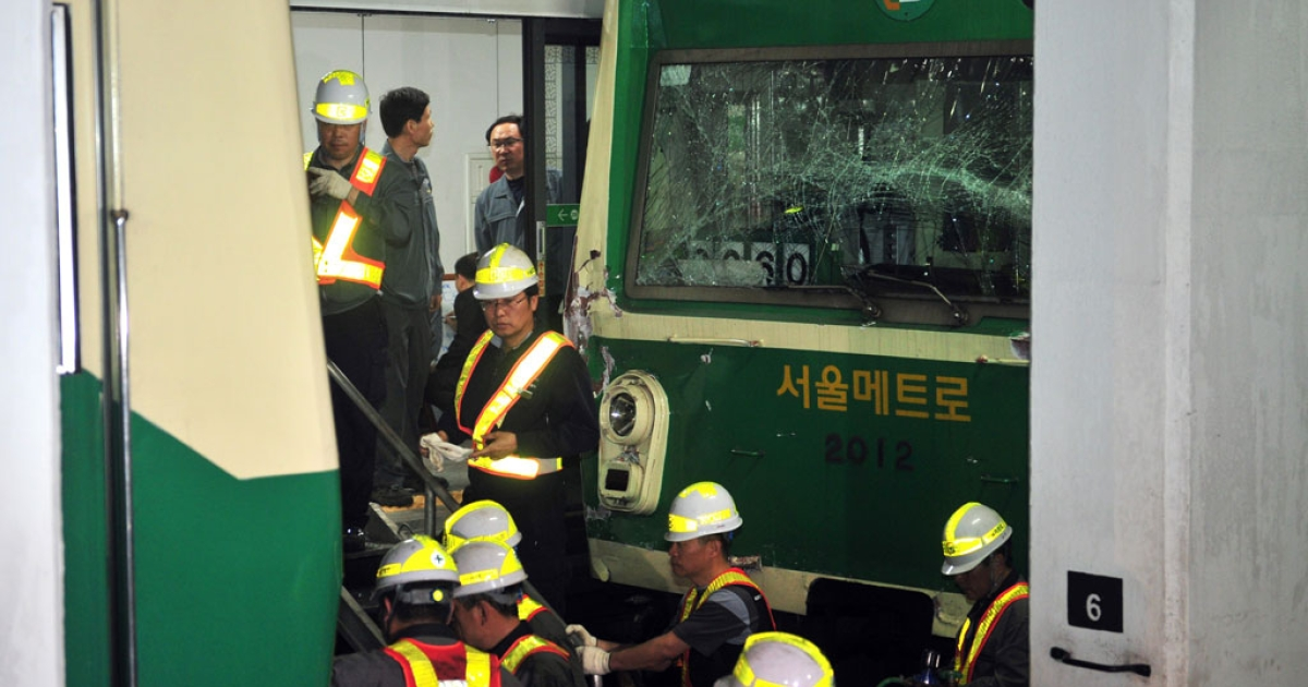 South Korean railway workers inspect two damaged trains after they collided in Seoul on May 2, 2014.</p>