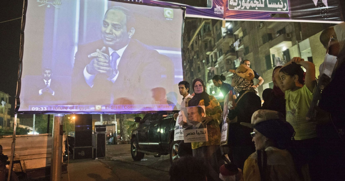 Egyptians watch Egypt's former army chief Abdel Fattah al-Sisi on a screen from the street in downtown Cairo on May 5, 2014, during his first television interview.</p>