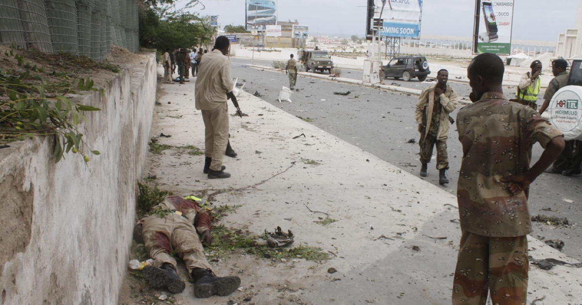 A Somali army soldier looks at the body of a fellow soldier during an attack on the Somali parliament in Mogadishu, on May 24, 2014.</p>
