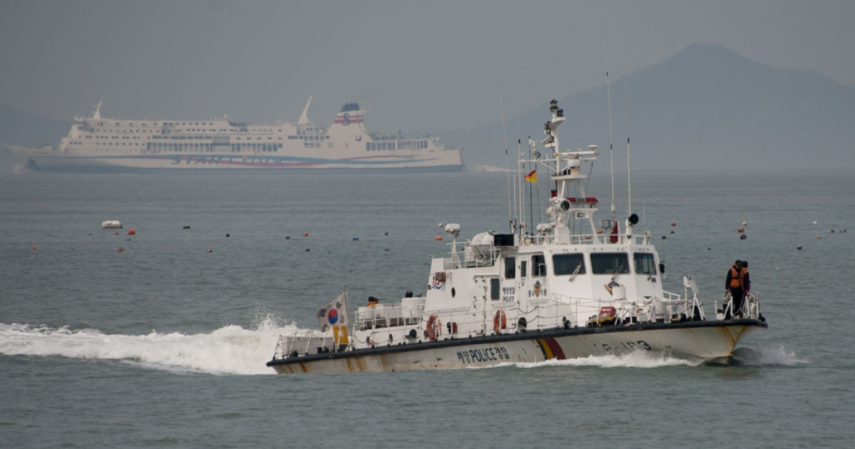 A coastguard boat carrying the bodies of victims recovered from the 'Sewol' ferry arrives at Jindo harbor on April 22, 2014.</p>
