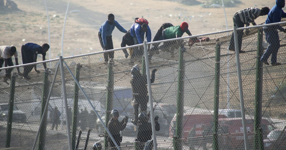 Spanish police officers try to prevent would-be immigrants from crossing a border fence separating Morocco from the north African Spanish enclave of Melilla on May 1, 2014.</p>