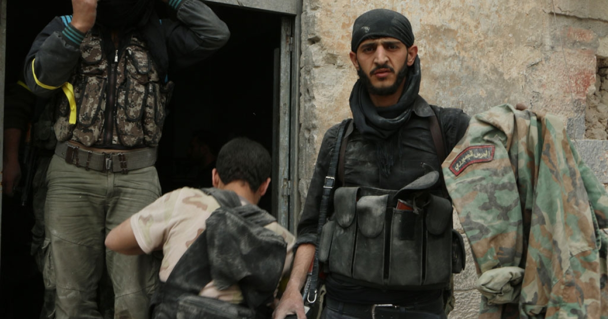Rebel fighters hold up a military jacket reportedly belonging to a presidential guard during clashes with government forces in Aleppo on April 17, 2014.</p>