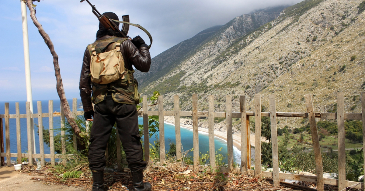 A rebel fighter stands on a ridge overlooking the Mediterranean sea reportedly in the village of Kasab, in the northwestern Syrian province of Latakia, on April 4, 2014.</p>