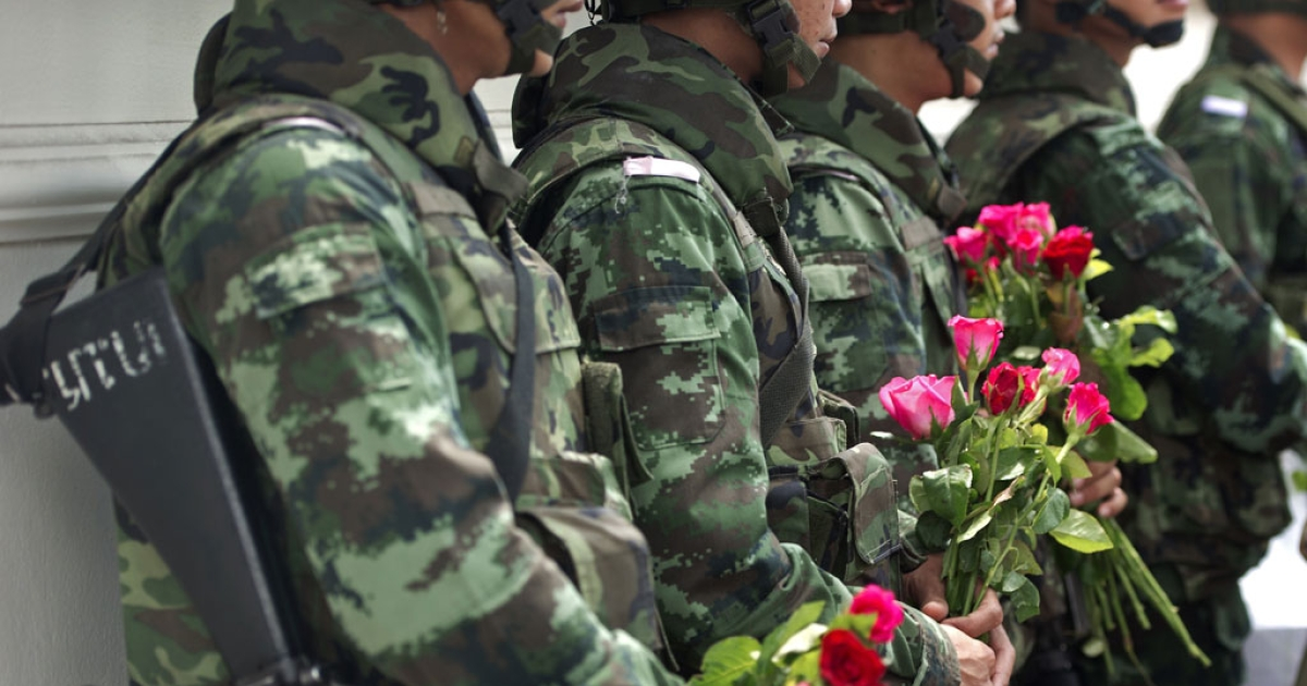Thai soldiers hold roses after receiving them from coup supporters at a military base in Bangkok on May 27, 2014.</p>