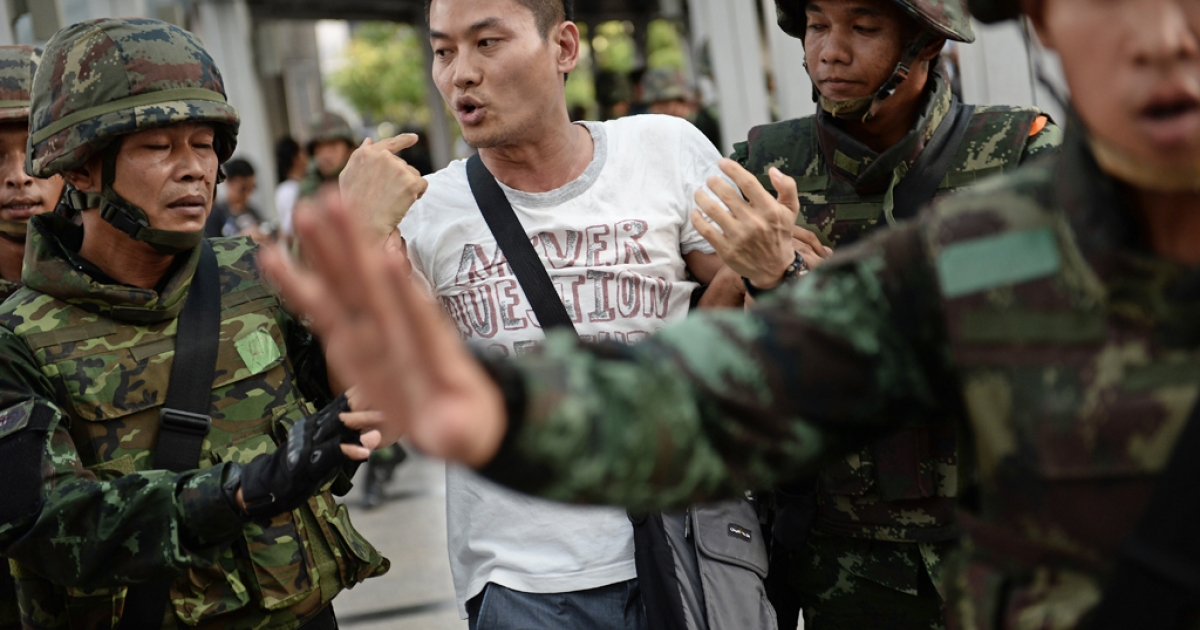 An anti-coup protester is taken away from the site of a gathering by Thai soldiers in Bangkok on May 24, 2014.</p>