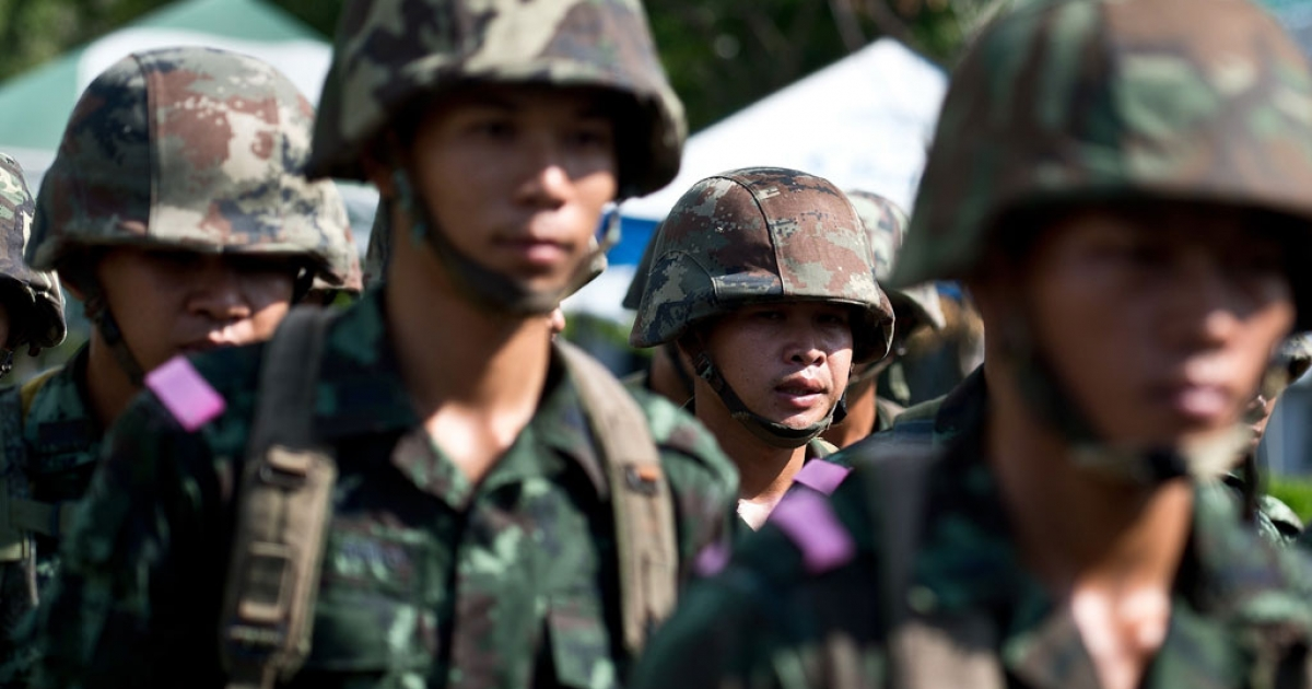 Thai Army soldiers keep guard during a meeting of the country's army chief general with the pro-government 'Red Shirts' leader and the anti-government protest leader in Bangkok on May 21, 2014.</p>