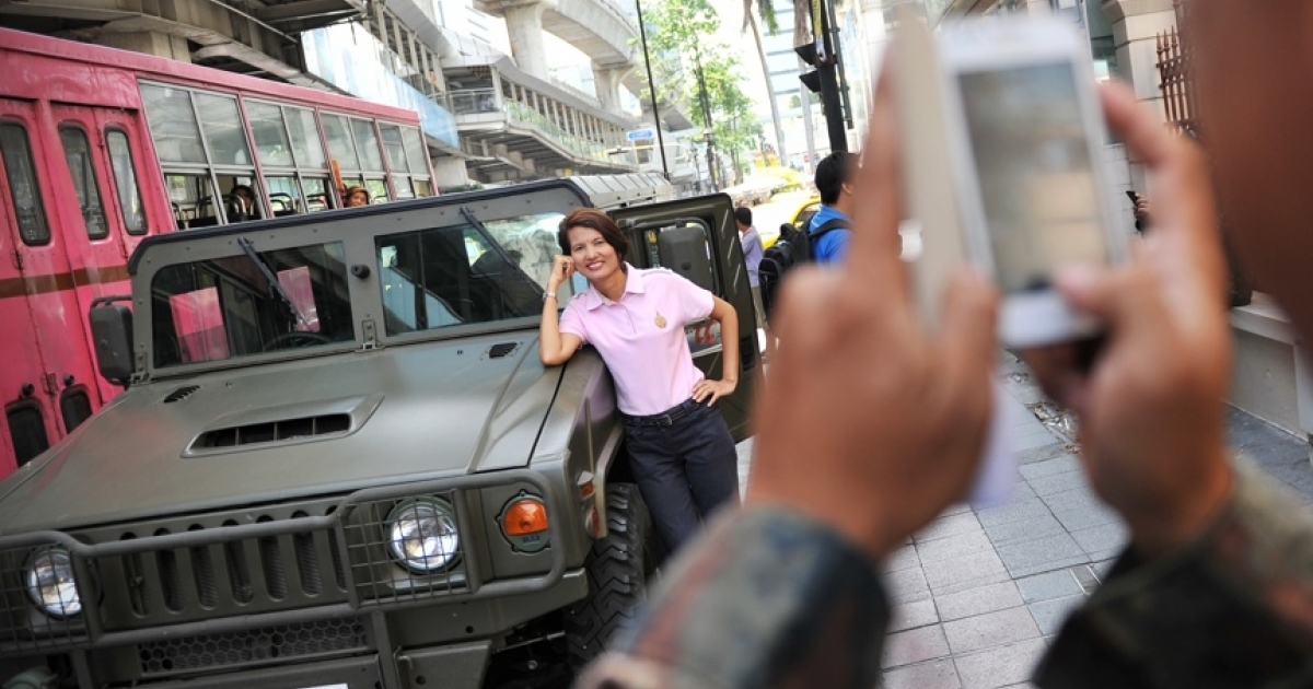 A woman poses for a photo as Thai army soldiers deploy on a downtown street after martial law was declared on May 20, 2014 in Bangkok.</p>
