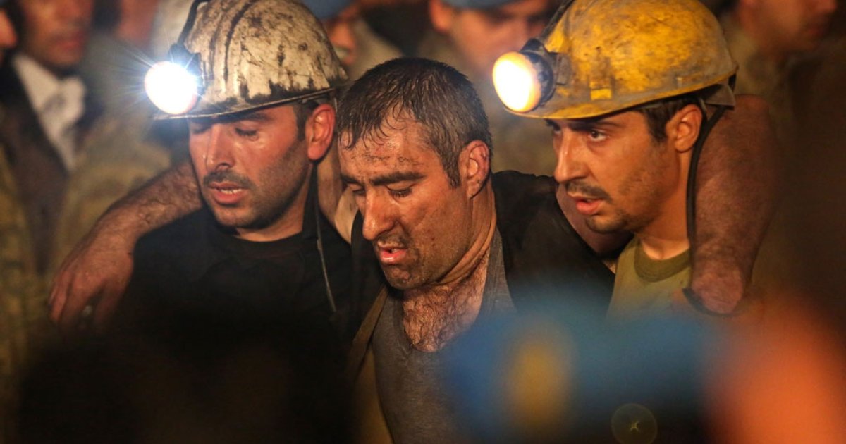 Miners are helped by rescue workers and friends from the coal mine on May 14, 2014 in Manisa, Turkey.</p>