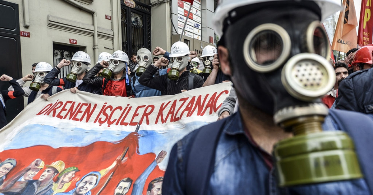 Turkish protesters wearing gas masks hold a banner reading 'Workers who resist win' as they march towards Taksim Square in Istanbul during a May Day rally on May 1, 2014.</p>