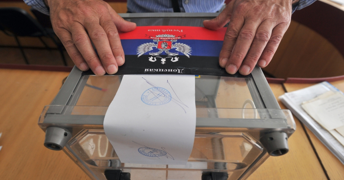 A member of the regional election commission glues a sticker depicting the flag of the self-proclaimed